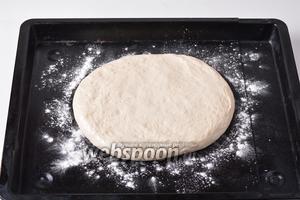 Противень посыпать мукой (1 ст. л.). Выложить тесто на противень и распределить руками в лепёшку толщиной 1,5-2 сантиметра.