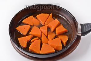Выложить кусочки тыквы в карамель. Готовить на небольшом огне 2-3 минуты.