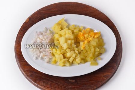 Лук очистить и нарезать 35 грамм мелкими кубиками. Картофель отварить в мундире, охладить, очистить и нарезать кубиками 100 грамм. Солёные огурцы очистить от кожуры и нарезать кубиками 60 грамм. 2 яйца очистить. Отделить желтки от белков. Желтки нарезать кубиками.