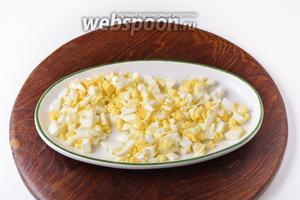 2 яйца отварить вкрутую, охладить, очистить и нарезать небольшими кубиками.