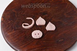 Из отложенного кружочка ветчины вырезать пятачок, ушки и хвост.