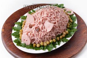 Прикрепить пятачок, ушки, хвост. Глаза можно сделать из изюминок, чернослива или маслин. Украсить салат зелёной петрушкой, консервированным горошком. Новогодний салат Свинья готов к подаче.