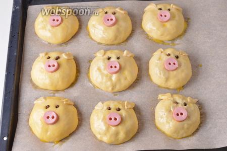 Выложить булочки швом вниз на противень, застеленный пергаментом. Оставить на 15 минут, а затем смазать разболтанной смесью из 1 желтка и воды (1 ч. л.). Из остатков теста сформировать ушки и прикрепить их на булочки, смазать их желтковой смесью. Оформить булочки, сделав «пятачок» из сосиски, а «глазки» из гвоздики.