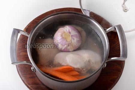 Возвратить части курицы в кастрюлю с чистой водой (0,7 литра). Добавить 1 очищенный целый лук (70 грамм), очищенные зубчики чеснока (2 штуки) и очищенную морковь (50 грамм), разрезанную вдоль на 4 части.