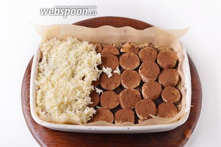 Сверху бананы равномерно посыпать второй столовой ложкой какао (лучше сыпать какао через мелкое ситечко). Сверху выложить массу из кокосовой стружки.