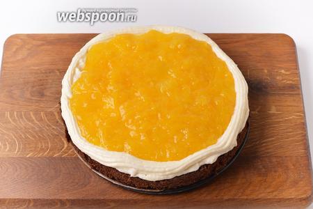 Смазать каждый корж частью крема. Кулинарным шприцем (насадка звёздочка) сделать с помощью крема бортик. Внутрь бортика выложить часть апельсинового конфи.