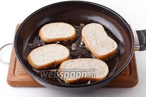 В сковороде разогреть 50 мл подсолнечного масла. Выложить ломтики батона начинкой вниз. Готовить на огне ниже среднего до золотистого цвета лука примерно 2-3 минуты.