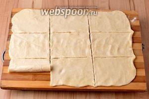 Разделить тесто на 2 части. Расктать каждую часть в прямоугольник размером 22х30 сантиметров. Разрезать прямоугольник на 9 частей и скатать каждую часть рулетиком.