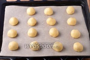 Разделить тесто на 15 частей (вес каждой части приблизительно 25 грамм), скатать каждую часть шариком и выложить на противень, застеленный пергаментом.