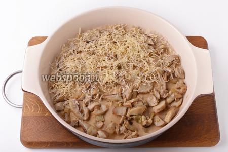 На дно формы диаметром 22 сантиметра выложить пергамент. На пергамент равномерно выложить подготовленные грибы. Сверху равномерно натереть 60 грамм сыра.