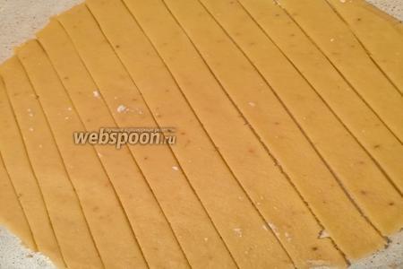 Из меньшей части раскатываем пласт и вырезаем полосочки по диаметру формы.