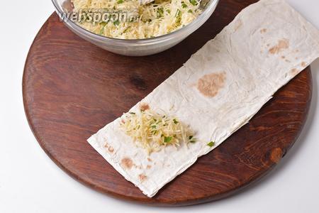 Лаваш нарезать полосками (приблизительно 6х27 см). На край каждой полоски выложить 1 столовую ложку сырной начинки.