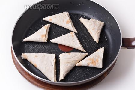 Разогреть сковороду с небольшим количеством подсолнечного масла (30 мл) и выложить в неё сформированные треугольники концами вниз. Обжаривать на небольшом огне по 2 минуты с каждой стороны.