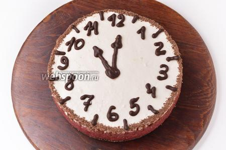 Перед подачей аккуратно отделить шоколадные цифры и стрелки от плёнки и выложить сверху на торт. Бока торта оформить натёртым шоколадом. Торт готов к подаче.