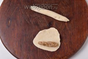 Раскатать каждую часть теста в круглую лепёшку толщиной 2 миллиметра. На край каждой лепёшки выложить ореховый брусок. Завернуть рулетом и тщательно защипнуть все концы. Прокатать образованную колбаску ладонью по доске, чтобы она стала длиной 12-13 см.