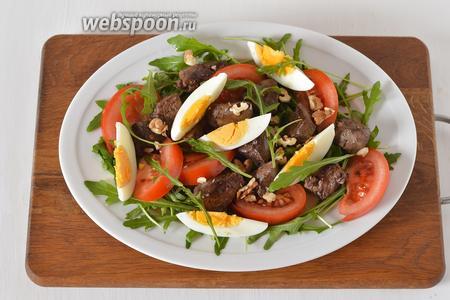 Собрать салат: на блюдо выложить промытую рукколу (1 пучок) и зелёный салат (20 грамм его можно порвать руками). Сверху разложить печень, помидоры, яйца. Полить заправкой, посыпать грецкими орехами и немедленно подавать.