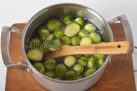 Влить кипяток (0,75 литра). Брюссельскую капусту 350 грамм промыть. Обрезать утолщения на конце каждого кочана, разрезать каждую капусту пополам и выложить в кастрюлю.