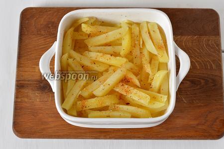 Форму смазать подсолнечным маслом (1 ст. л.). Выложить картофель в форму, посыпать приправой для картофеля (1 ч. л.), частью соли и перемешать.