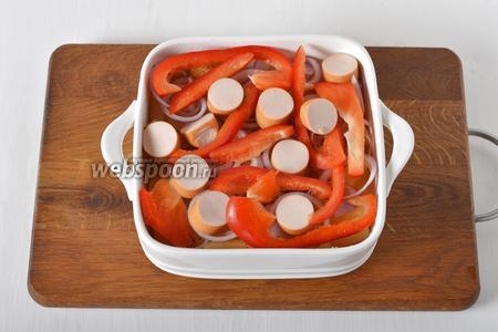 Сверху выложить очищенный и нарезанный кольцами лук 50 грамм, нарезанный полосками сладкий перец (1 половинка), очищенные от плёнки и нарезанные кусочками 2 сосиски. Выложить в разогретую до 200°С духовку и готовить 25 минут.