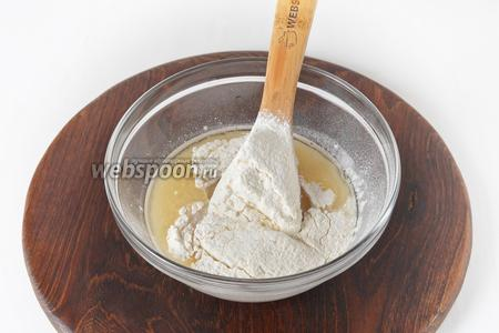 Добавить 2 столовых ложки подсолнечного масла, 200 грамм просеянной муки.