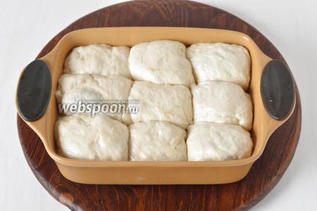 Выложить пирожки в смазанную подсолнечным маслом форму. Оставить в тёплом месте на 20 минут, накрыв полотенцем.
