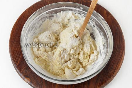 Постепенно добавить 210 грамм муки, просеянной с содой (0,5 ч. л.). Возможно, муки вам понадобится немного меньше или больше (это будет зависеть от величины яиц и влажности творога).