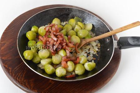К подготовленному луку выложить капусту, бекон, яблочный уксус (0,5 ч. л.). Приправить солью (0,2 ч. л.), перемешать и готовить 3-4 минуты.