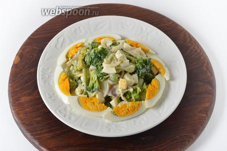 Выложить салат на блюдо. Украсить дольками яйца.