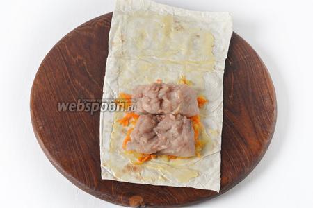 С одного края лаваша выложить 1 полную столовую ложку луково-морковной смеси. Сверху — 2 кусочка филе скумбрии. На этой стадии филе можно дополнительно сбрызнуть небольшим количеством лимонного сока.