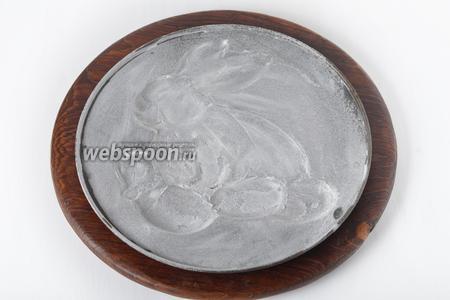 Специальную форму с изображением-углублением в виде кролика смазать тонким слоем сливочного масла и посыпать тонким слоем муки (по 1 столовой ложке).