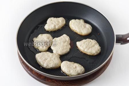 На сковороде разогреть часть подсолнечного масла. Аккуратно, с края, набирать тесто столовой ложкой (ни в коем случае не перемешивайте поднявшееся тесто, чтобы оно не осело). Выложить тесто в виде оладьев на подготовленную сковороду. Обжарить с обеих сторон до золотистого цвета.