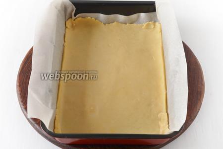 Раскатать 1 часть теста и выложить его в застеленную пергаментом форму размером 20х30 сантиметров.