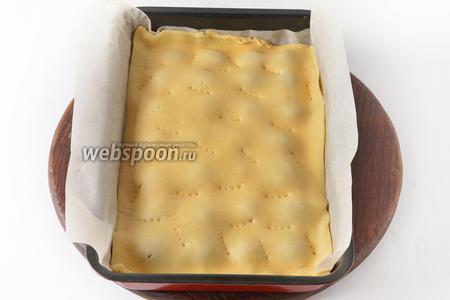 Накрыть сверху тонко раскатанной второй частью теста (для удобства раскатывайте тесто на пергаменте и с ним переносите на начинку). Поколоть его вилкой.