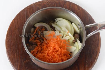 Влить в кастрюлю 2 столовых ложки подсолнечного масла, добавить очищенный и нарезанный полукольцами лук (75 грамм), а также очищенную и натёртую на крупной тёрке морковь (60 грамм). Готовить, помешивая, 2-3 минуты.