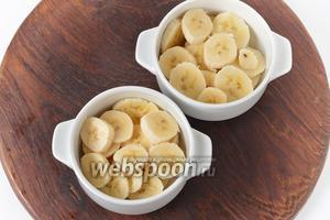 Одну большую форму или порционные формочки смазать сливочным маслом (10 грамм). Выложить в форму нарезанные кружочками бананы и полить их лимонным соком (1 ст. л.).