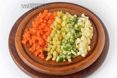 Картофель (100 грамм) и морковь (60 грамм) отварить в кожуре до готовности, охладить, очистить и нарезать небольшими кубиками. Яблоки очистить от кожуры и сердцевины, нарезать кубиками (50 грамм). Огурец нарезать кубиками (100 грамм).