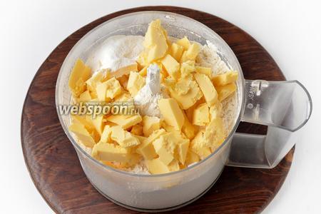 В чашу кухонного комбайна (насадка металлический нож) выложить просеянную пшеничную муку (225 грамм), 1 щепотку соли, 10 грамм разрыхлителя и нарезанное кусочками холодное сливочное масло (115 грамм). Измельчить до образования крошки.