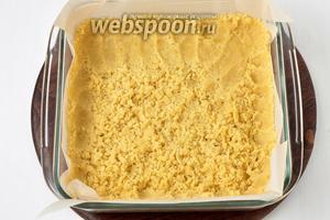 Форму (25х25 сантиметров) выстелить пергаментом. 2/3 части теста натереть на крупной тёрке в форму и равномерно распределить его вилкой по всей форме. Сформировать дно и бортики пирога, слегка прижимая тесто к форме.