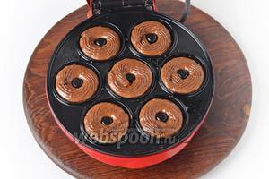 Специальную форму для пончиков (электрическую или силиконовую для выпекания в духовке) смазать тонким слоем растительного масла. Выложить тесто в формы. Очень удобно это сделать, поместив тесто в кулинарный мешок с круглой или звёздчатой насадкой.