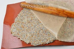 Раскатать тесто между двумя листами пергамента или между силиконовым ковриком и пергаментом до толщины 2-3 миллиметра. Лист пергамента и силиконовый коврик перед работой лучше смазать тонким слоем подсолнечного масла (1 ст. л.).