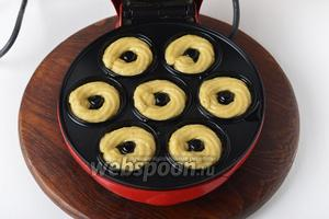 Выложить тесто порционно в специальные силиконовые формы для выпекания пончиков в духовке или электрическую форму для приготовления пончиков. Для этого очень удобно поместить тесто в кулинарный мешок с насадкой «маленькая звёздочка» и с его помощью аккуратно наполнять формочки.