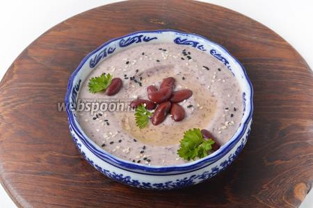 Выложить хумус в глубокую посуду или пиалу, украсить петрушкой (15 грамм), зёрнами фасоли, полить сверху остальным подсолнечным маслом. Хумус из фасоли готов к подаче.