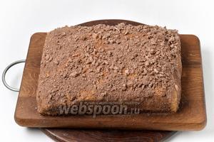 Печенье (лучше шоколадное) раскрошить и посыпать им верх и бока коржа. Отправить торт в холодильник минимум на 12 часов. За это время крем загустеет и очень хорошо пропитает песочные коржи. Торт хорошо нарезается и получается очень нежным.
