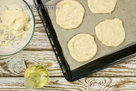 Противень выстилаем пергаментом и, смазав руки растительным маслом, начинаем формировать заготовки под мини-пиццы. Отрываем от теста кусок, приблизительно размером с яйцо, и делаем заготовку в виде лепёшки-ватрушки. Получается 2 противня пицц — около 12 штук.