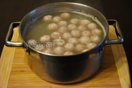 Фрикадельки опустить в несильно кипящий бульон (2 литра).