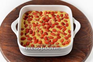Форму (размером 15х15 сантиметров) смазать подсолнечным маслом (10 мл). Выложить тесто в форму. Сверху выложить промытую и обсушенную землянику (70 грамм) и слегка вжать её в тесто.