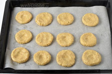 Разделить тесто на 12 частей, сформировать из них лепёшки и выложить на противень, застеленный пергаментом. В центре каждой лепёшки сделать углубление.