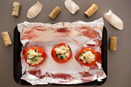 Смешайте заправку с готовым рисом. Заполните помидоры, по желанию посыпьте тёртым сыром (40 грамм). Разместите на промасленный противень и запекайте в духовке при температуре 180°C 20 минут.