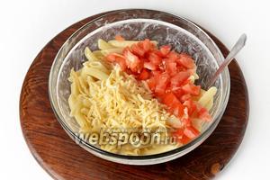 Помидоры промыть и нарезать 80 грамм кубиками. 80 грамм сыра натереть на средней тёрке. Соединить макароны, помидоры и половину подготовленного сыра. Перемешать.