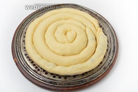 Выложить рулетики в подготовленную форму улиткой. Накрыть пищевой плёнкой и оставить в тёплом месте на 45 минут.